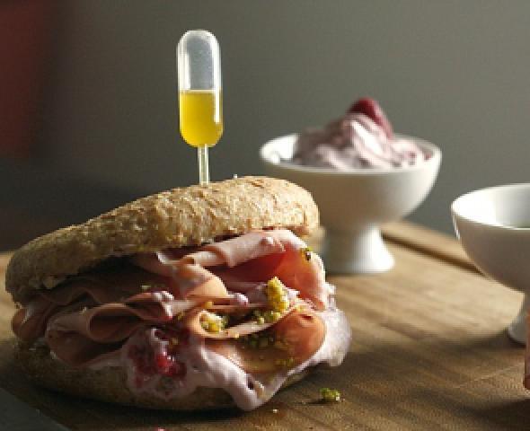 Siringa per olio su panino con mortadella e pistacchi