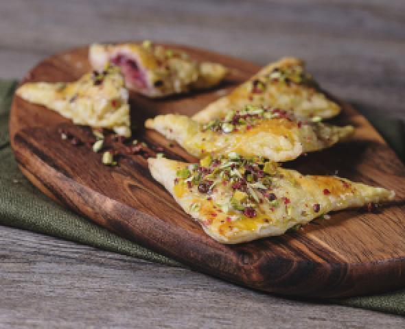 Petits triangles de pâte feuilletée farcis à la mortadelle et à l'oignon caramélisé, aux grains de pistaches et de poivre rose
