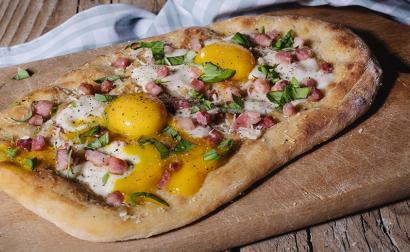Pizza alla carbonara con uova, pancetta, scaglie di pecorino e basilico