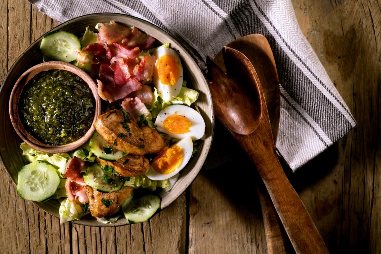 Bowl con uova, avocado, petali di bacon e petto di pollo