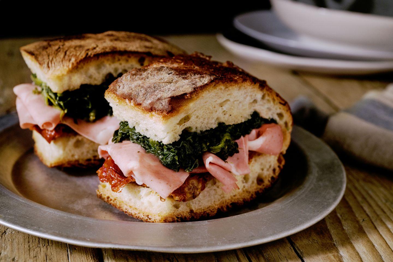 Sandwich di focaccia con mortadella, cime di rapa e pomodori secchi