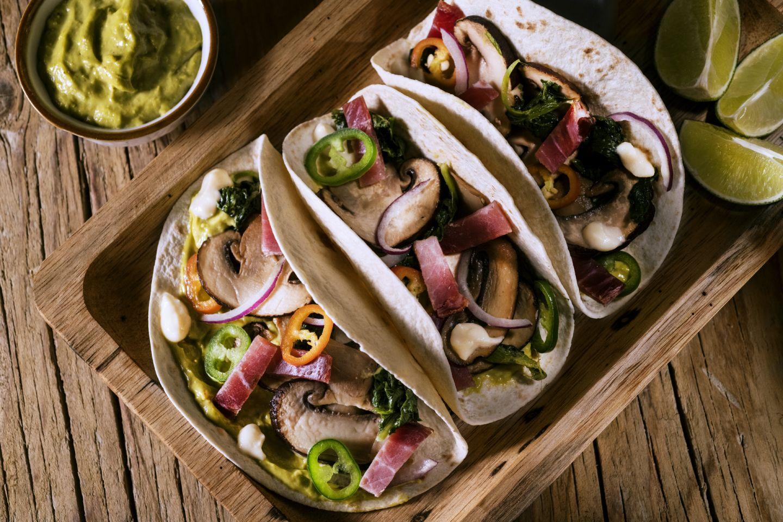 Tacos con salsa nachos, petali di speck, cipolle e avocado