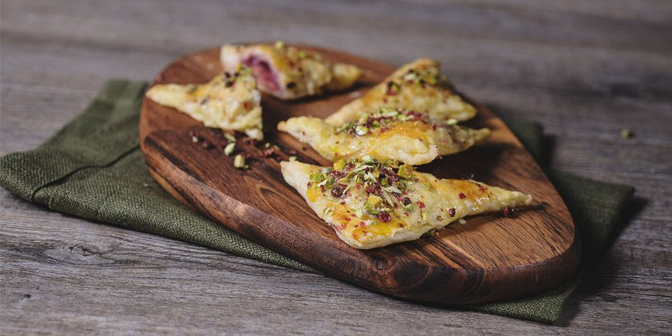Puff pastry triangles filled with mortadella and caramelized onion, garnished with chopped pistachios and pink pepper