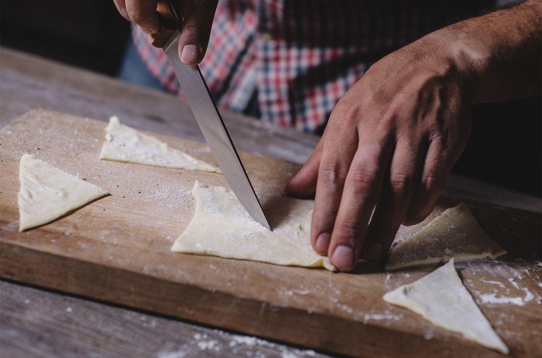 Petits triangles de pâte feuilletée farcis à la mortadelle et à l'oignon, aux grains de pistaches